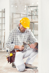Builder kneeling using a chisel and mallet