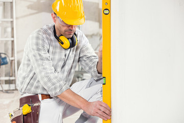 Builder using a spirit level to measure a wall
