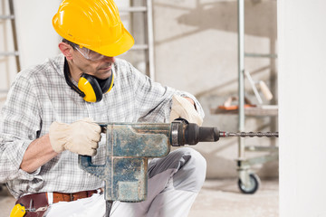 Builder using a handheld power drill