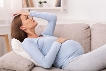 Pregnant Woman Touching Forehead Having Migraine Lying On Sofa