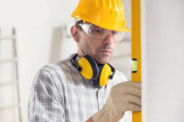 Builder using a spirit level on a vertical wall