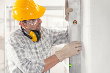 Builder or contractor using a large spirit level