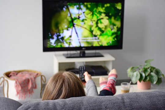 Young woman watching television with subtitles while sitting comfortably on sofa at home in living room. Nature, green, documentary, tv screen