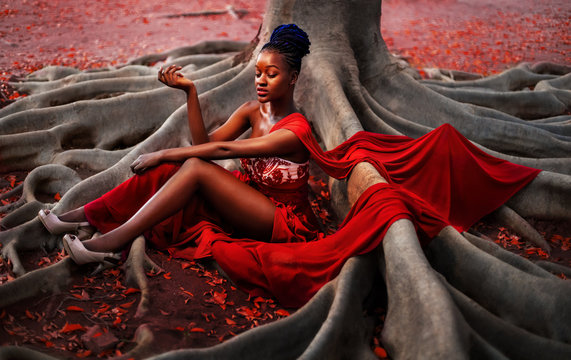 Creative photo of a young African woman in a long evening red dress.