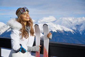 Closeup portrait of beautiful skier girl wearing mask and holding ski, enjoying winter holidays