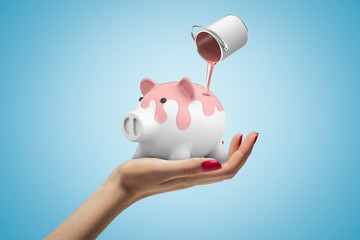 Closeup of woman's hand facing up holding white piggy bank and can of pink paint in air poring...