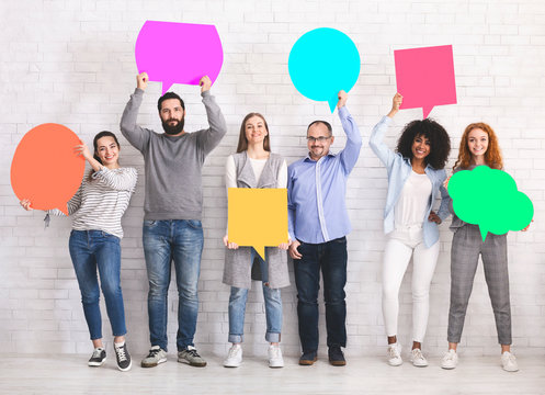 Group of diverse friends holding blank colorful speech bubbles