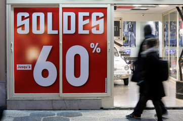 A discount sale sign is seen on a storefront window on the eve of the start of winter sales in Nice