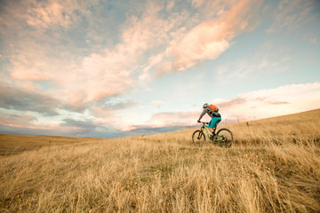 One woman enjoys the first rideable window over Jones Pass on the Continental Divide Trail in Colorado. As the snow melts off the high alpine trails, rocky singletrack is revealed on the Rocky Mountains for a short window before winter hides them under her blanket again.
