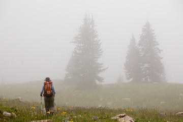 One woman hiking through the fog on her way to Twilight Peak in the Weminuche Wilderness near Silverton, Colorado