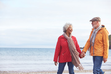 Senior Couple Hold Hands As They Walk Along Shoreline On Winter Beach Vacation Wall mural