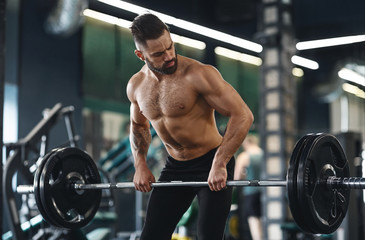 Wall Mural - Muscular athlete exercising with heavy barbell at gym