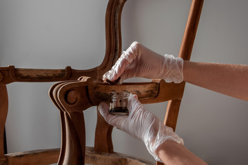Obraz processing furniture stain with a swab made of lint-free cloth. all parts backrest, armrest, leg. Renovation of old furniture as an antique Victorian old wooden armchair. - fototapety do salonu