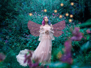 Art photo of a fairy fairy in a pink dress in the forest with fireflies