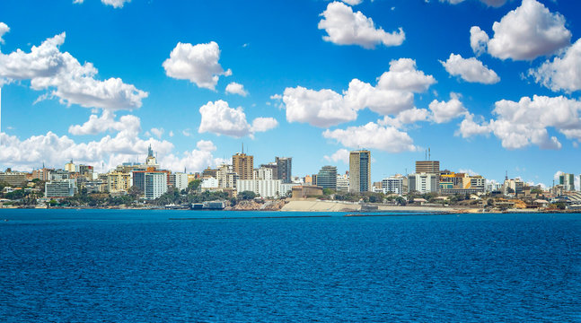 View of the Senegal capital of Dakar, Africa. It is a city panorama taken from a boat. There are large modern buildings and a blue sky with clouds.