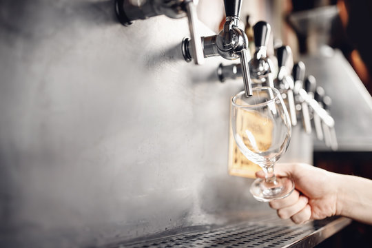Beer taps cider wineglass raw in pub. Selective focus, dark background