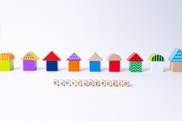 "Cubes with letters saying ""Baukindergeld"", the German word for money for building a house for families in front of a row of houses built of toy colorful toy blocks"