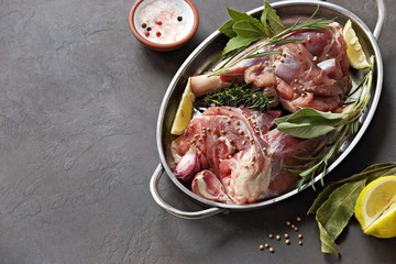 Raw lamb shanks with herbs and spices. Flat layot on dark concrete background. Copy space