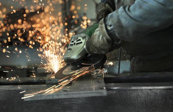 Un carpentiere ripulisce con la mola un pezzo di acciaio