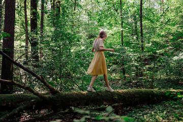 Woman walking on fallen tree in forest