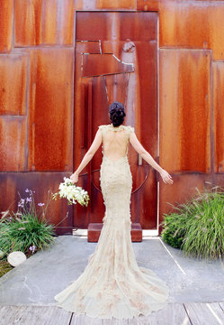 Rear view of bride with bouquet standing outdoors