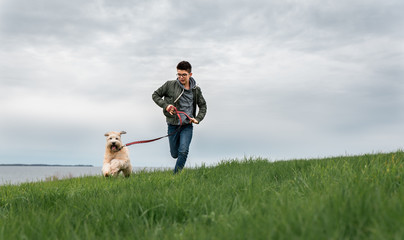 Teenage boy running up a grassy hill with his dog on cloudy day.