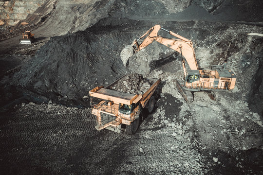 Excavator Loading Coal Truck from Aerial View