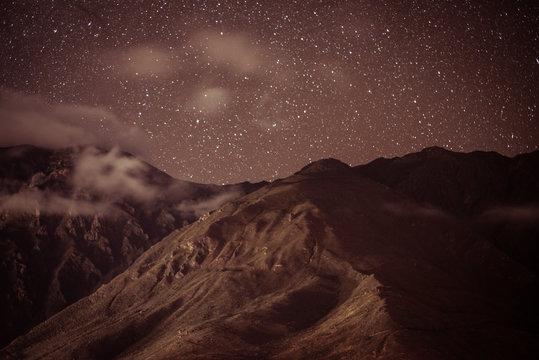 Stars shine bright above beautiful remote mountain range in peru