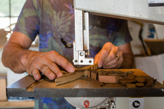 Close-up view of man crafting wood art on band saw