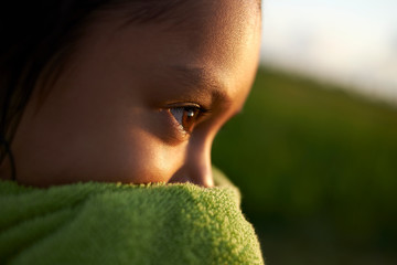 Close up of girl wrapped in green towel during sunset
