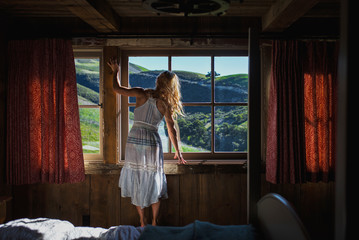 Woman looking out of cabin window at beautiful landsacpe