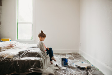 Young girl sitting on bed in freshly painted white room