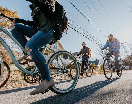 A group of friends ride their bikes through a village in Maine