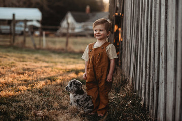 toddler baby boy standing outside by a barn with a puppy
