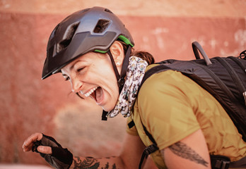 a female cyclist wearing a helmet laughs and smiles with joy