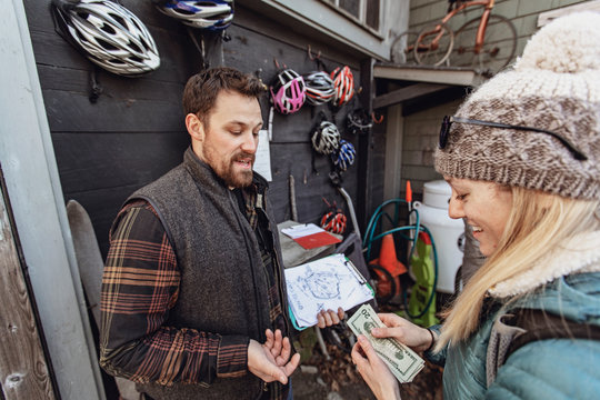 A young woman pays for a bike rental in cash