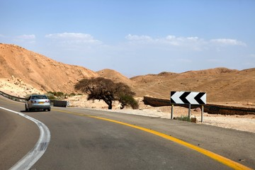 car on a highway that runs along the Dead Sea from one side and Edom Mountains at Arava Desert from the other in Israel. Wall mural