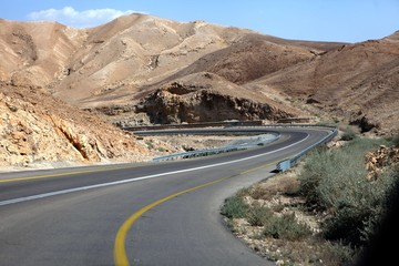 curvy sandy road on a highway that runs along the Dead Sea from one side and Edom Mountains at Arava Desert from the other in Israel. Wall mural