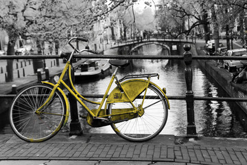 Tuinposter Fiets A picture of a lonely azure bike on the bridge over the channel in Amsterdam. The background is black and white.