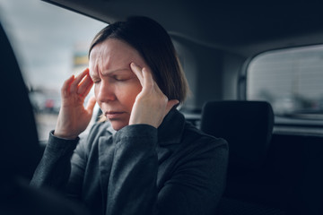 Businesswoman having migraine headache in company car