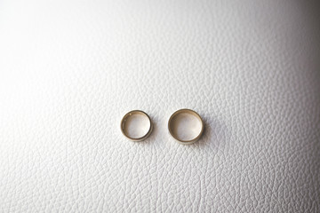 Fotobehang a pair of golden wedding rings on white leather background