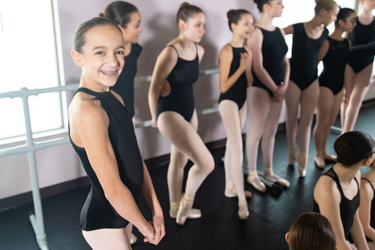 Young girl in ballet dance class smiles with group of dancers behind her