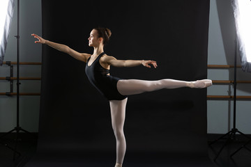 Ballet dancer poses as photo is taken with studio lights