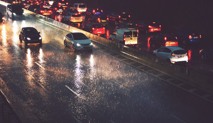 car traffic by city highway in rainy night
