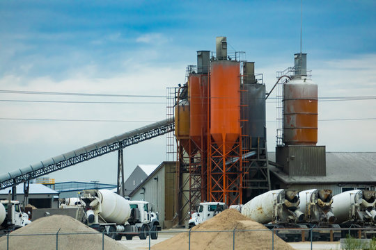 A wide angle view of a concrete batching and manufacture plant with aggregate conveyor, cement silos, industrial architecture and parked mixer trucks