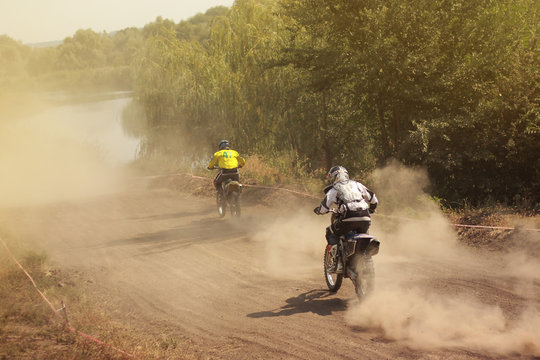 Two motorcyclists catching up with each other in the dust, view from the back, motocross sport competition