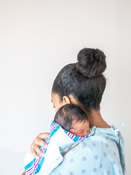 A mixed race African American mother faces away from the camera wearing a hospital gown holds her brand new infant baby over her shoulder hugging and cradling him as he sleeps in his blanket swaddle.