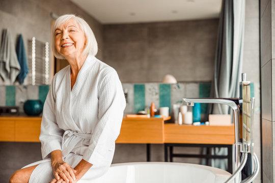 Cheerful elderly woman relaxing in spa salon
