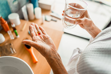 Elderly woman holding pills and glass of water