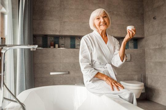 Smiling elderly woman holding jar of cream
